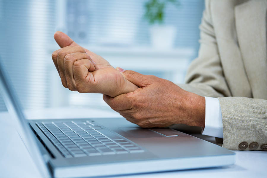 Businessman holding wrist with pain sitting at computer