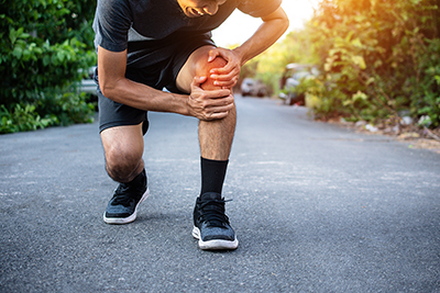 Runner bent over holding extremely painful knee.
