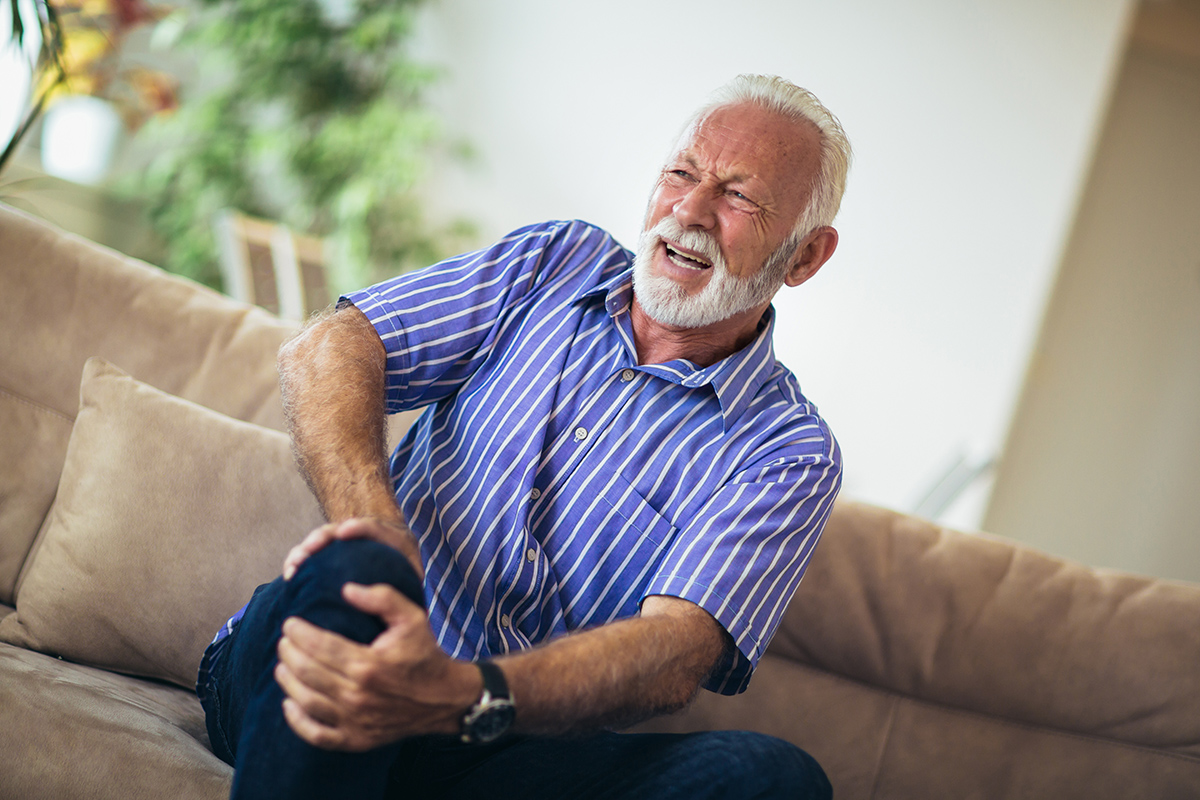 Senior man with chronic knee pain clutching his knee